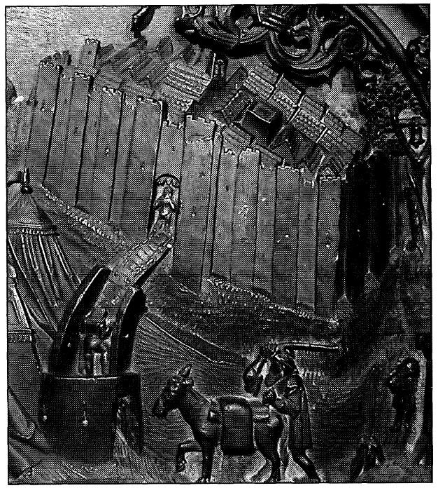 Figura 1. Detalle del Real de Santa Fe en el tablero de la sillería del coro bajo de la Catedral de Toledo en el que se representan las murallas almenadas, las torres, las cavas y una puerta de entrada con su baluarte, su través y su puente levadizo. García Pulido y col. (2005)